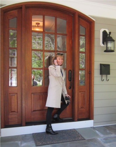 Alice V. McKenna, framed by wooden door, on phone.