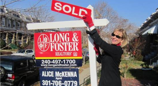 Alice standing with sold sign