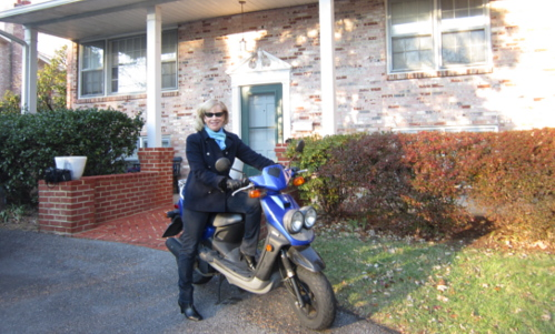 Alice McKenna on blue scooter in front of house